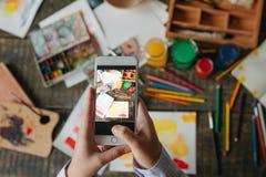 Телефон обнесенное решеткой места в суде рук женщины принимая фото работы акварели Творческий процесс художника работы стоковое фото rf