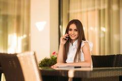 Телефон пользы длинных волос женский пока она ждет заказ в кафе стоковое фото