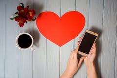 Телефон пользы женщины во время перерыва на чашку кофе Стоковое Изображение
