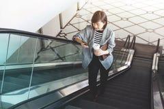 Телефон пользы работницы умный пока эскалатор Стоковое Фото
