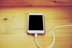 Телефон помещен в деревянном столе И заткните внутри батарею b стоковая фотография rf