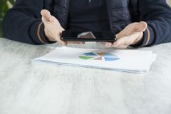 Телефон руки человека с диаграммой стоковое фото