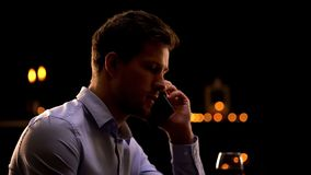 Телефон серьезного бизнесмена говоря, ослабляя в ночном клубе после дня тяжелой работы стоковые фотографии rf