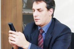 телефон удерживания бизнесмена бесшнуровой Стоковые Изображения