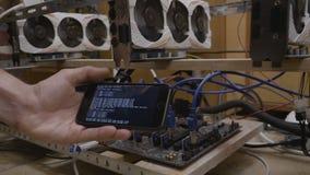 Телефон удерживания руки молодого человека дела с ходом приложения горнорабочего близко к снаряжению минирования ethereum gpu - акции видеоматериалы