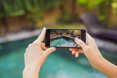Телефон удерживания руки на предпосылке бассейна в гостинице камера фото на экране конец вверх по смартфону владением руки приним стоковая фотография