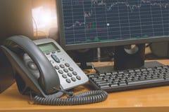 Телефон IP с клавиатурой компьютера и монитор показывают финансовую диаграмму на экране Стоковое Изображение