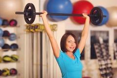 телохранителя женщина работая с штангой в классе фитнеса Женская разминка в спортзале с штангой стоковое фото