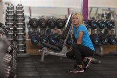 телохранителя Сильная женщина пригонки работая с весом весы девушки поднимаясь в спортзале стоковые фото