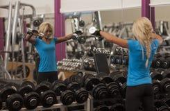 телохранителя Сильная женщина пригонки работая с гантелями весы девушки поднимаясь в спортзале стоковое фото rf