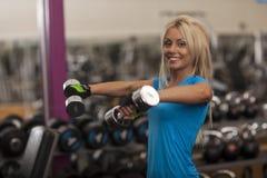 телохранителя Сильная женщина пригонки работая с гантелями весы девушки поднимаясь в спортзале стоковое изображение rf