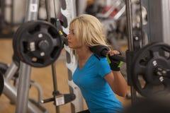 телохранителя Сильная женщина пригонки работая с штангой весы девушки поднимаясь в спортзале стоковое изображение rf