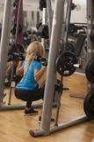 телохранителя Сильная женщина пригонки работая с штангой весы девушки поднимаясь в спортзале стоковые изображения
