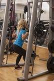 телохранителя Сильная женщина пригонки работая с штангой весы девушки поднимаясь в спортзале стоковые фотографии rf