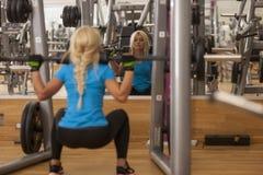 телохранителя Сильная женщина пригонки работая с штангой весы девушки поднимаясь в спортзале стоковое изображение