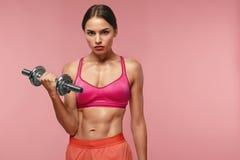 телохранителя Тренировка женщины с гантелью на розовой предпосылке стоковые фото