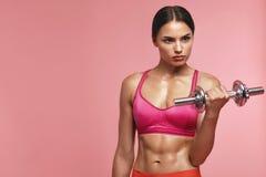 телохранителя Тренировка женщины с гантелью на розовой предпосылке стоковое фото rf