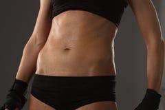 Тело молодой атлетической девушки на темной предпосылке Стоковое Фото