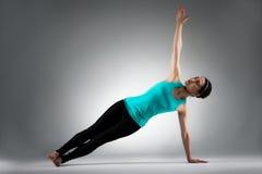 Тело разминки девушки фитнеса спортзала в серой предпосылке Стоковое фото RF
