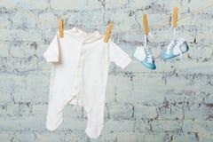 Тело ` s детей белое и голубые ботинки на веревочке против белой кирпичной стены Стоковое Фото