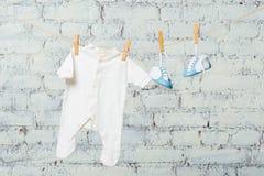 Тело ` s детей белое и голубые ботинки на веревочке против белой кирпичной стены Стоковая Фотография RF