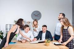 Тема дело и сыгранность Группа в составе молодые кавказские работники офиса людей созывая собрание, брифинг, работая с бумагами стоковое изображение