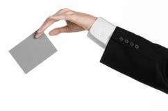 Тема дела и рекламы: Человек в черном костюме держа серую пустую карточку в руке изолированной на белой предпосылке в студии Стоковые Фотографии RF