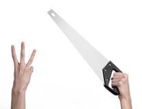 Тема конструкции: вручите держать пилу с черной ручкой на белой предпосылке изолированный Стоковые Фотографии RF