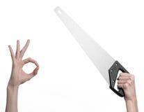 Тема конструкции: вручите держать пилу с черной ручкой на белой предпосылке изолированный Стоковое Фото