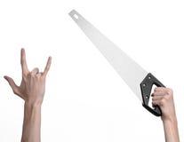 Тема конструкции: вручите держать пилу с черной ручкой на белой предпосылке изолированный Стоковое Изображение
