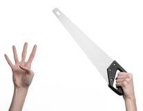 Тема конструкции: вручите держать пилу с черной ручкой на белой предпосылке изолированный Стоковые Фото