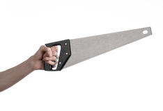Тема конструкции: вручите держать пилу с черной ручкой на белой предпосылке изолированный Стоковое фото RF