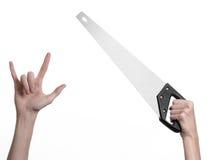 Тема конструкции: вручите держать пилу с черной ручкой на белой предпосылке изолированный Стоковые Изображения RF
