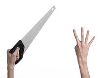 Тема конструкции: вручите держать пилу с черной ручкой на белой предпосылке изолированный Стоковая Фотография