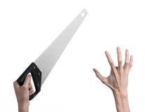 Тема конструкции: вручите держать пилу с черной ручкой на белой предпосылке изолированный Стоковая Фотография RF