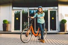 Тема, который нужно работать на велосипеде Молодая кавказская женщина приехала на экологически дружелюбный велосипед перехода к о стоковые изображения