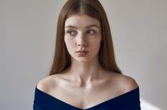 Тема красоты: портрет красивой маленькой девочки с веснушками на ее стороне и носить голубое платье на белой предпосылке в studi стоковое фото rf