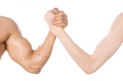 Тема культуризма & фитнеса: рука армрестлинга тонкая и большая сильная рука изолированная на белой предпосылке в студии Стоковые Фотографии RF