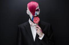 Тема клоуна и хеллоуина: Страшный клоун с розовыми волосами в черной куртке с конфетой в руке на темной предпосылке в студии Стоковая Фотография