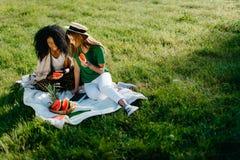 Тема пикника 2 alluring очаровывающ африканские и кавказские подруг беседуя и просматривая через мобильный телефон пока Стоковые Изображения RF