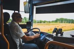 Тема профессия транспорта водителя и пассажира Человек в водителе солнечных очков a управляет туристской региональной шиной внутр Стоковые Фотографии RF