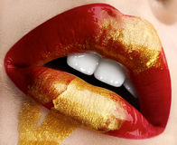 Тема состава макроса и конца-вверх творческая: Красивые толстенькие женские губы с красным цветом и краска золота, влажное влияни Стоковое Изображение