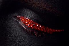 Тема состава макроса и конца-вверх творческая: красивый женский глаз с черными диамантами кожи и красного цвета, заретушированным Стоковое Фото