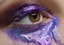 Тема состава макроса и конца-вверх творческая: красивый женский глаз с фиолетовыми пигментом и sequins, заретушированным фото Стоковое фото RF