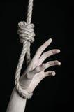 Тема суицида и депрессии: человеческая смертная казнь через повешение руки на петле веревочки на черной предпосылке Стоковые Изображения RF