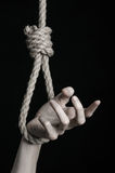 Тема суицида и депрессии: человеческая смертная казнь через повешение руки на петле веревочки на черной предпосылке Стоковые Изображения