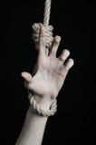 Тема суицида и депрессии: человеческая смертная казнь через повешение руки на петле веревочки на черной предпосылке Стоковое Изображение RF