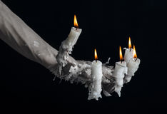 Тема хеллоуина: на руке носить свечу и капать расплавленный воск на черноте изолировали предпосылку стоковое фото