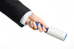 Тема химической чистки и дела: человек в черном костюме держа голубую липкую щетку для очищая одежд и мебель от пыли Стоковое фото RF