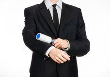 Тема химической чистки и дела: человек в черном костюме держа голубую липкую щетку для очищая одежд и мебель от пыли Стоковые Изображения
